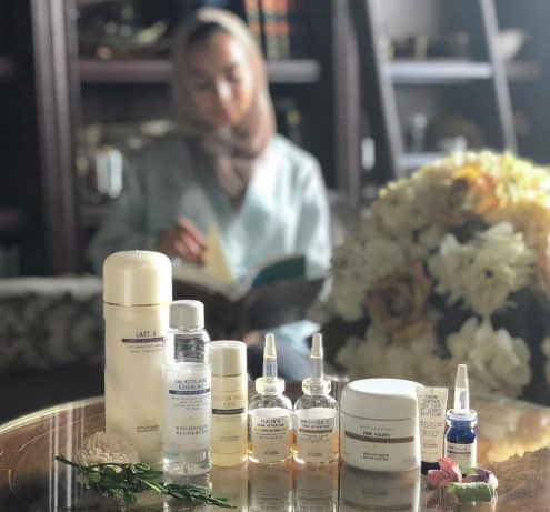 foreground of beauty products on a table with sunlit woman reading in the background