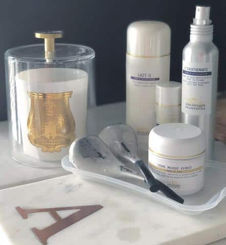 white tray with products arranged on top and a white and gold candle beside it