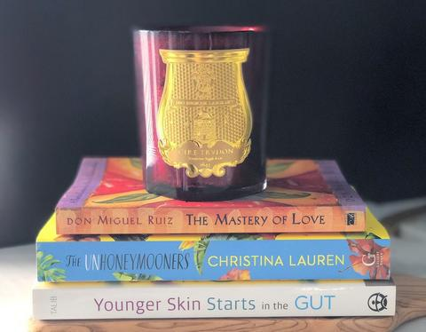 stack of three books with candle on top