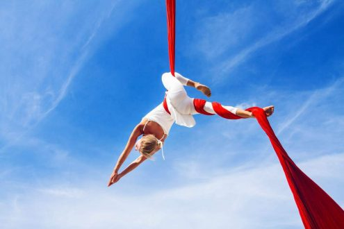 trapeze artist dressed in white hanging form red silks against a blue sky