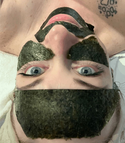 prone patient, upside-down, smiles up knowingly at camera while wearing shiny green spa mask