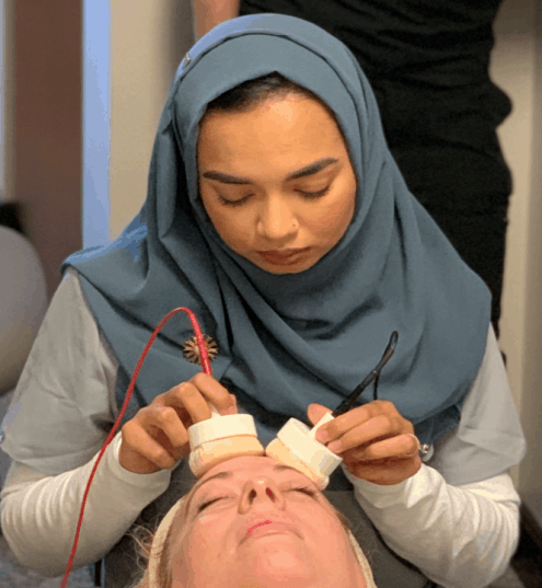 aesthetician hold two sponge pads to a prone patient's face during facial