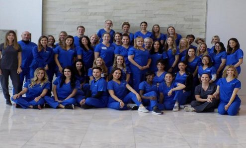group photo of about 30 people wearing royal blue scrubs, smiling against grey marble floor and wall